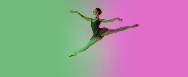 光。ネオンのグラデーションピンクグリーンの壁に分離された若くて優雅なバレエダンサー。アート、モーション、アクション、柔軟性、インスピレーションのコンセプト。柔軟なバレリーナ、無重力ジャンプ。