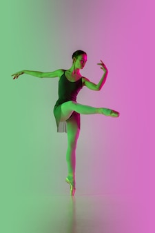 Luce. giovane e graziosa ballerina isolata sul muro rosa-verde sfumato in neon. arte, movimento, azione, flessibilità, concetto di ispirazione. ballerina flessibile, salti senza peso.