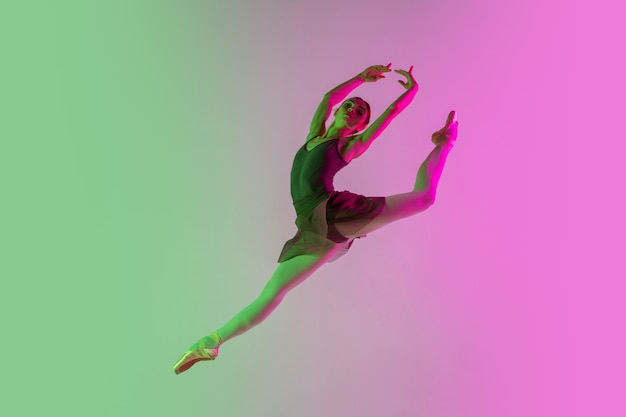 Light. young and graceful ballet dancer isolated on gradient pink-green  wall in neon. art, motion, action, flexibility, inspiration concept. flexible ballerina, weightless jumps.