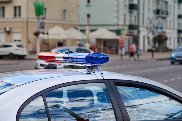 Крупный план lightbar полицейской машины против улицы города