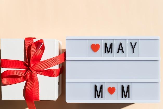 ライトボックスとプレゼントボックス。おめでとう母の日。タイトルのライトボックスとパステル調の背景にママ。幸せな母の日のコンセプトです。コピースペース