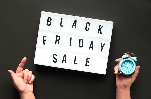 Lightbox text black friday on black paper with hands holding alarm