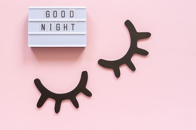 ライトボックスのテキストおやすみなさいと装飾的な木製の黒いまつげ
