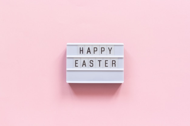 Lightbox text happy easter on pink paper background.