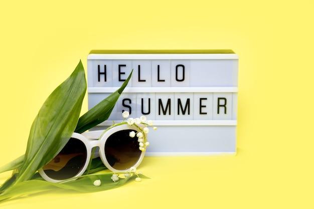 黄色の背景にメッセージhellosummerのライトボックス。夏、旅行、休暇の概念。