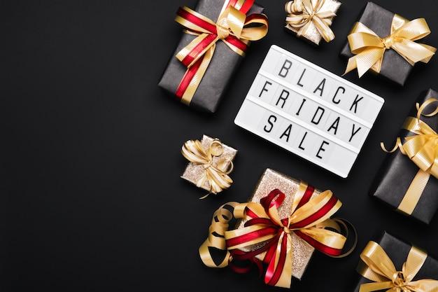Лайтбокс с текстом черная пятница продажи и золотые подарочные коробки на черном фоне.