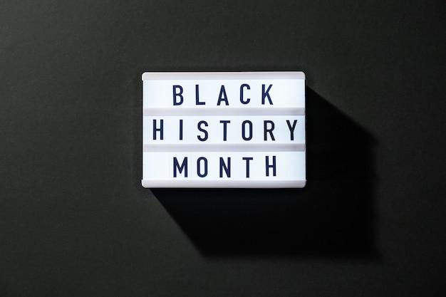 어두운 검정색 배경에 black history month라는 텍스트가 있는 라이트박스. 메시지 기록 이벤트. 빛