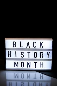 거울 반사가 있는 어두운 검정색 배경에 black history month라는 텍스트가 있는 라이트박스. 메시지 기록 이벤트. 빛