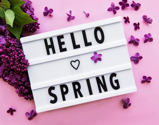 Лайтбокс с текстом hello spring и сиреневыми цветами на розовом, вид сверху