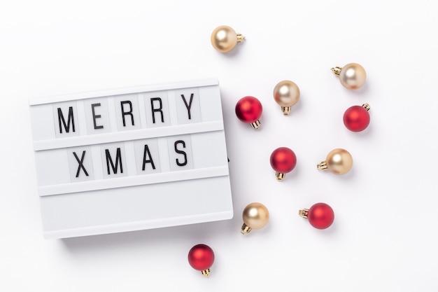 テキストmerryxmasと白い背景の上の金色と赤のクリスマスボールとライトボックス