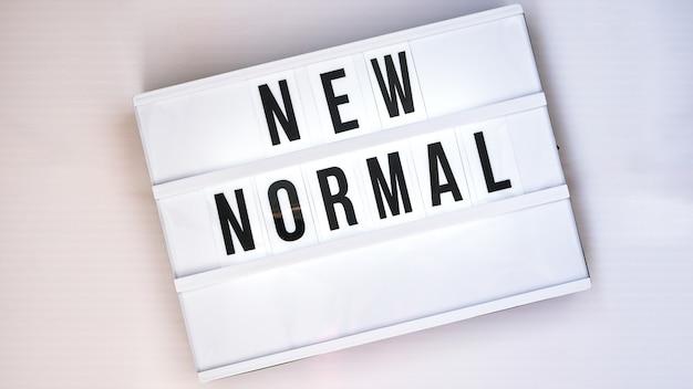 New normal이라는 텍스트가 있는 라이트박스. 학교로 돌아가다. 사회적 거리두기. 학교 검역 개념입니다. 공간을 복사합니다. 코로나 2차 유행