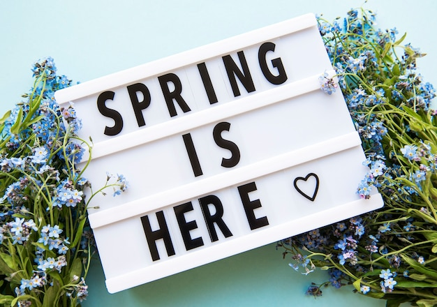Spring is here 텍스트가있는 라이트 박스와 녹색 테이블에 꽃이 아니라 꽃다발