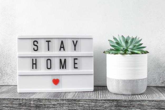 木製のテーブルにテキストstayhomeとサボテンの植物が付いたライトボックス。安全を保ち、家のコンセプトの中にとどまる