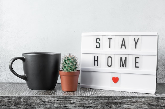 木製のテーブルにテキストstayhome、マグカップ、サボテンの植物が描かれたライトボックス。安全を確保し、家にいるコンセプト