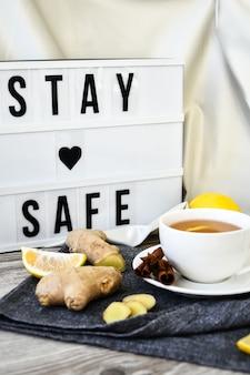 텍스트가 있는 라이트박스 stay safe 생강 뜨거운 면역 강화 비타민 천연 음료 감귤류, 꿀, 재료를 나무 배경에 소박한 스타일로 포함합니다. 카모마일 차. 건강한 개념