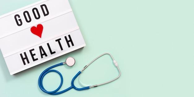 라이트 박스 좋은 건강 단어와 파란색 청진 기 건강 및 의료 개념의 관리입니다.