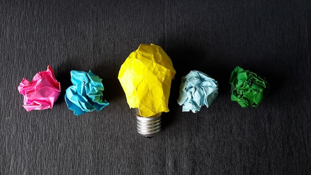 Lightbulb and crumpled papers