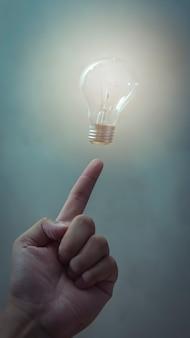 남자의 손가락, 비즈니스 및 아이디어 개념 위에 떠있는 전구