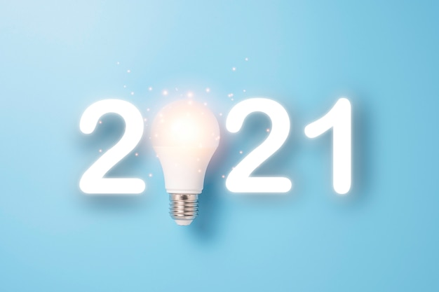 Lightbulb glowing for 2021 merry christmas and happy new year. starting idea concept.