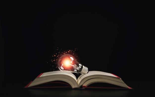 概念を読んで研究した後、創造的な思考のアイデアのために暗い背景の上に本に光る電球。