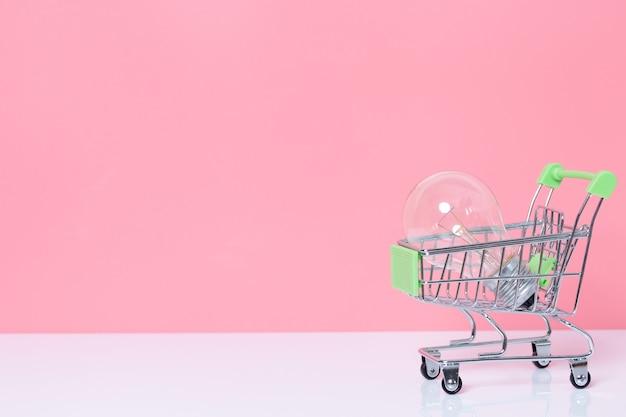 コピースペースとピンクの背景にショッピングカートの電球。アイデアのコンセプトとインスピレーション。