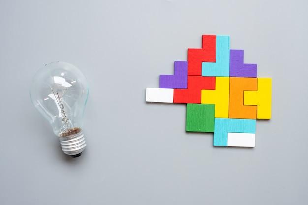 회색에 화려한 나무 퍼즐 조각으로 전구. 새로운 아이디어, 창의적, 혁신, 상상력, 영감, 솔루션, 전략 및 논리 개념