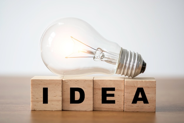Lightbulb on wooden cubes block which print screen idea wording.