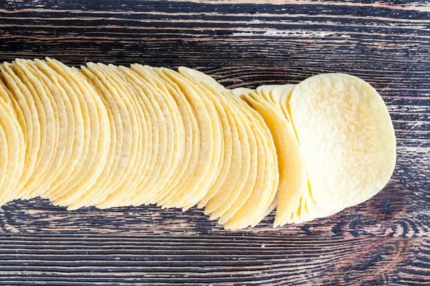 Тонкие картофельные чипсы светлого цвета из картофельного пюре, натуральные для вредного продукта на столе