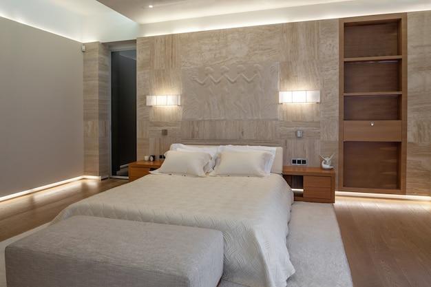 大理石の壁とダブルベッドの近くの彫刻パネルのある照明付きのベッドルーム