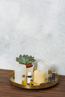 Lighted candle; cactus plant; mustard seed; la stone and essential oil on copper plate over the wooden desk