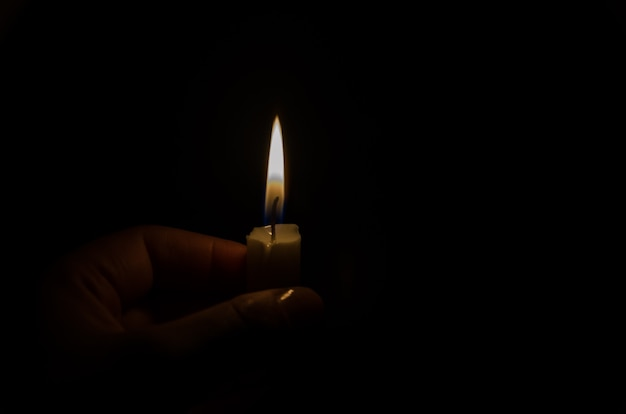 Lighted candle in the dark