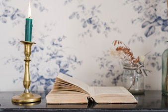 Lighted candle over the candlestick holder and an open book on desk against wallpaper