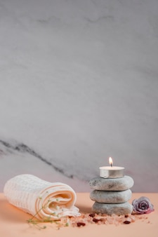 Lighted candle over the spa stones with napkin; rose and himalayan salts on peach colored backdrop against grey background
