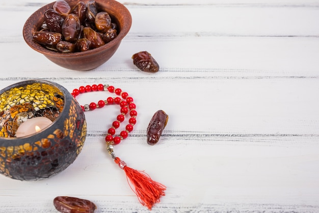 Lighted candle with bowl of juicy dates and red prayer beads on white wooden background