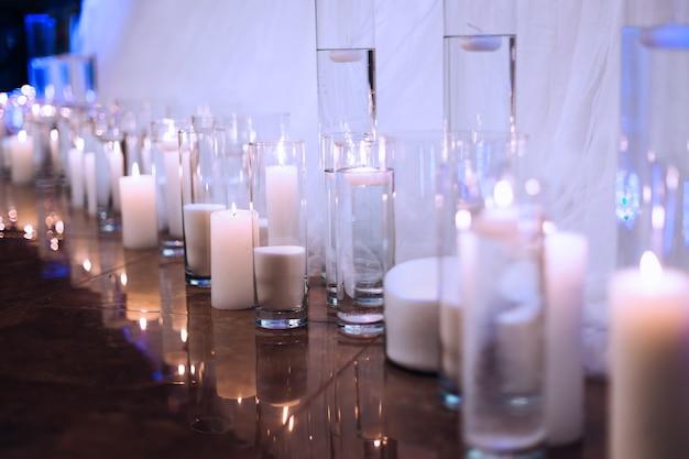 Зажженные свечи перед столом со скатертью маленькие свечи в прозрачных вазах с водой