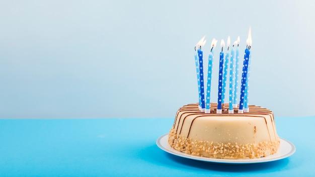 Зажженные свечи над вкусным тортом на голубом фоне