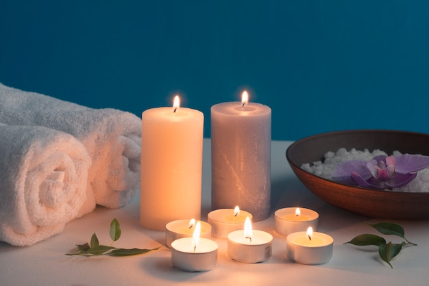 Lighted candles, rolled up towel and bath spa salt on table