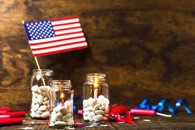 Lighted candles and usa flag in the candies jar on wooden desk