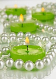 구슬이 있는 조명이 켜진 촛불을 닫습니다.