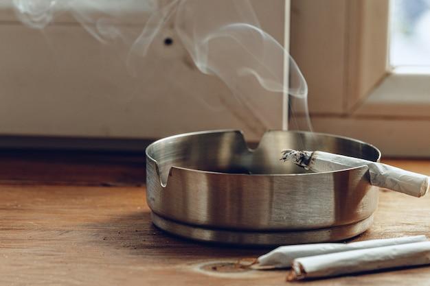 Зажженная сигарета в металлической пепельнице крупным планом