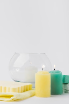 Lighted colorful candles with sponge and napkin against white backdrop