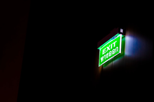 The lighted exit sign is in the dark.
