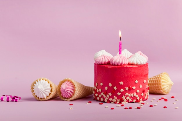 Lighted number one candle on delicious red cake with star sprinkles and waffle cones against purple backdrop