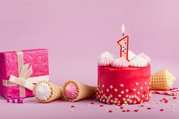 Lighted number one candle on delicious red cake with star sprinkles; waffle cones and gift box against purple backdrop