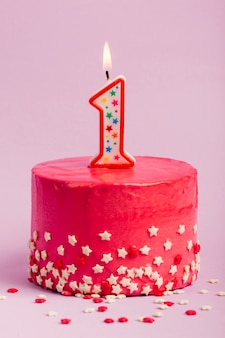 Lighted number one candle on red cake with star sprinkles against purple backdrop
