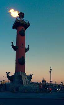 日没時にロストラ柱に火をつけた。サンクトペテルブルク、ヴァシリエフスキー島。