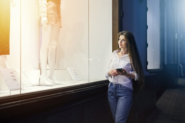 Lighted showcase of clothing store near stands young woman with smartphone and looks inside