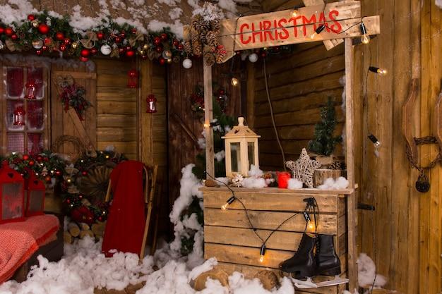 さまざまなクリスマスの装飾が施された家の中の照明付き木製クリスマスブース。