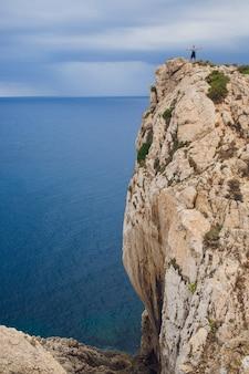 Маяк на мысе форментор в побережье северной майорки, испания. художественный восход и закат пейзаж молодой человек на горе
