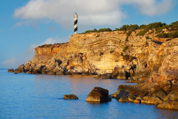 青い海の崖の上に沈む夕日の灯台